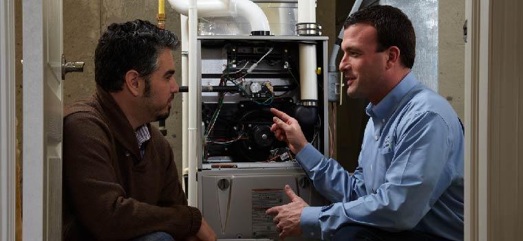 Heating technician showing customer furnace.