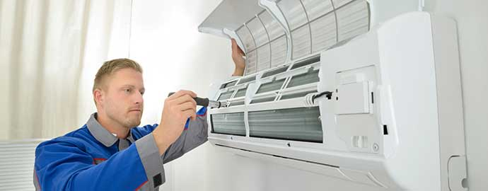 Technician working on ductless heating and cooling system